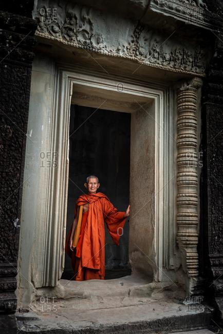 SIEM REAP, CAMBODIA - 16 November 2013: Monk in Angkor Wat gallery doorway.