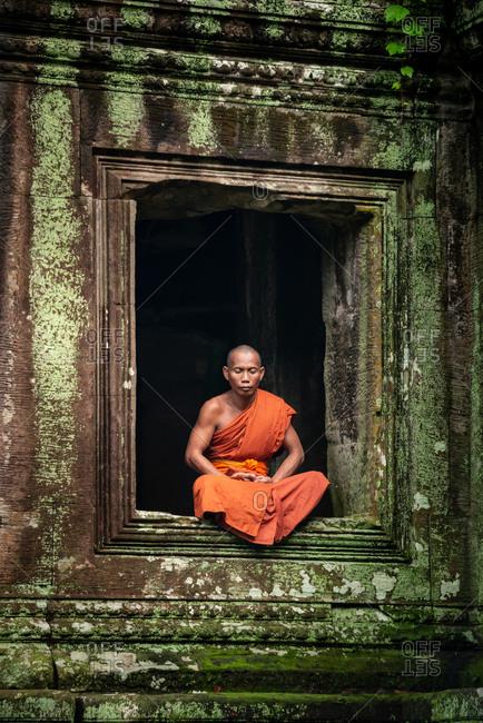 SIEM REAP, CAMBODIA - 10 August 2013: Monk meditates in window Angkor Wat