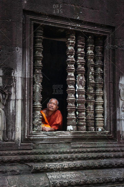 SIEM REAP, CAMBODIA - 14 SEPTEMBER 2010:  Monk in Angkor Wat window.