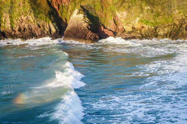 Waves crash at Caerfai Bay, St David's, Pembrokeshire, Wales, UK.
