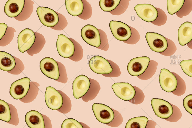Pattern of halved avocados on pink background