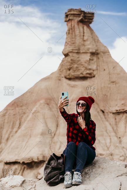 Spain- Navarre- Portrait of female tourist takingselfiein front of sandstone rock formation inBardenasReales