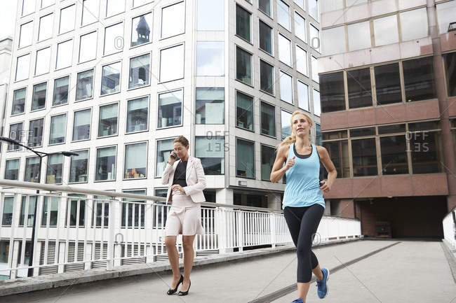 Woman running by businesswoman talking through phone on footbridge against modern office building in city