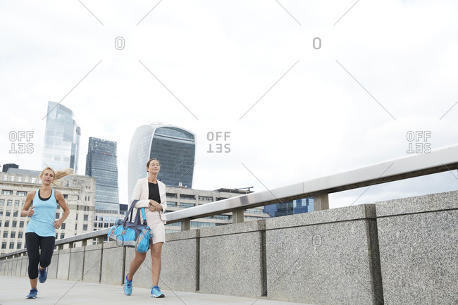 Woman running by businesswoman carrying bag on footbridge in city against clear sky