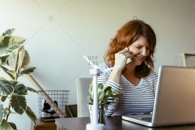 Woman talking on mobile phone while working on laptop at home