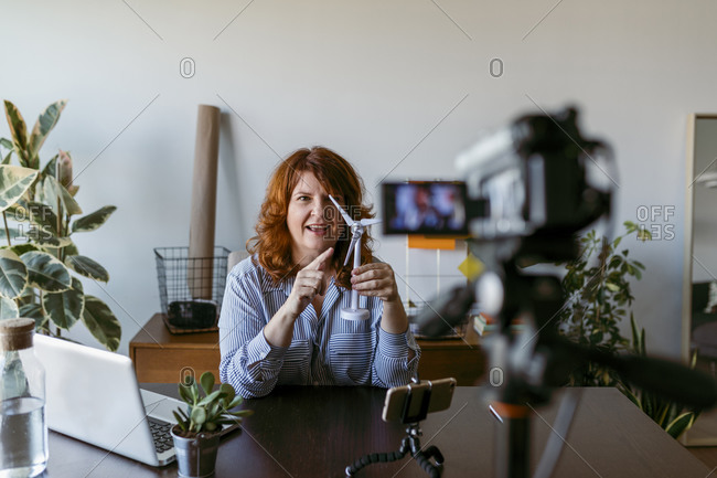 Woman making vlog with home video camera while sitting by table at home