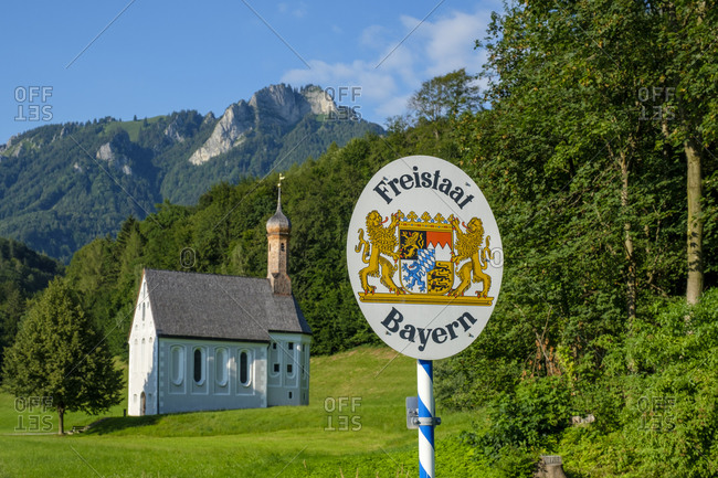 August 6, 2020: Germany- Bavaria- Nussdorf- State border information sign with Kreuzkirche in background