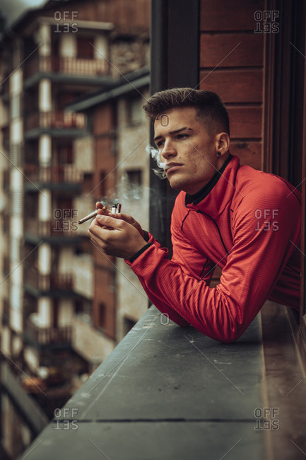 Young man smoking marijuana joint while looking out of window