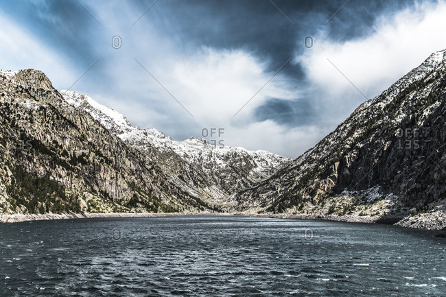 Lake in winter with snowy mountains and cloudy sky in background