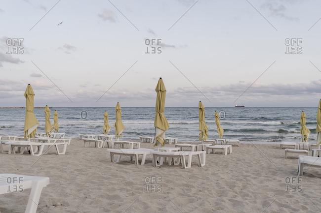 Beach umbrellas and deck chairs on empty beach at dusk