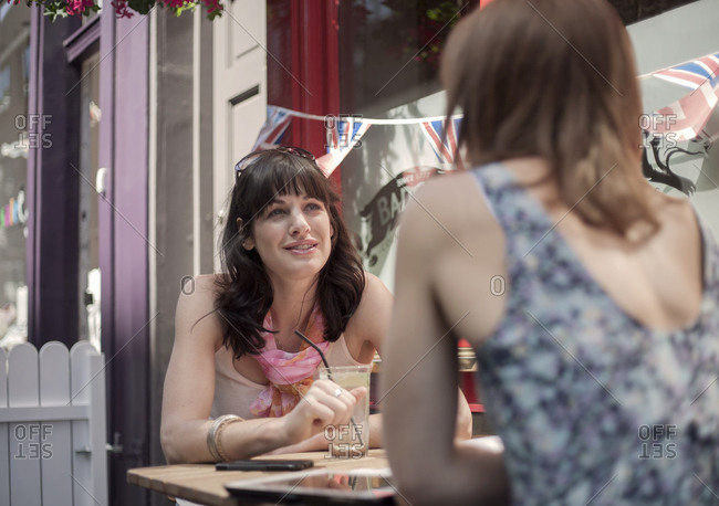 Woman talking with female friend while sitting at pub