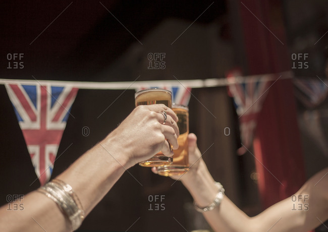 Female friends toasting beer glasses while enjoying weekend at pub