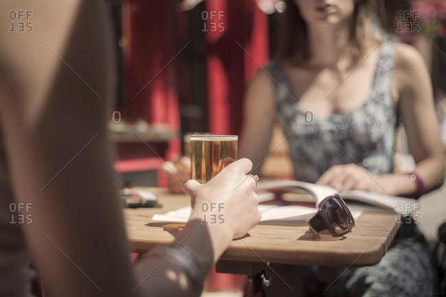 Woman having beer with female friend at pub