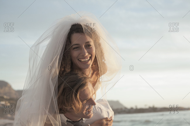 Newlywed couple in wedding dress enjoying at beach during sunset