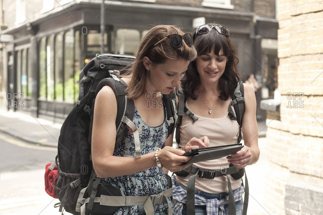 Female backpackers using digital tablet for guidance map while exploring city