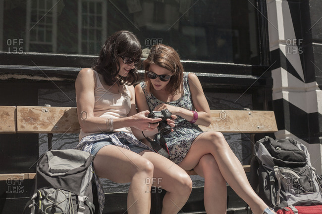 Curious woman looking at camera held by female friend while sitting on bench in city