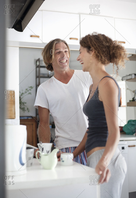 Couple laughing while preparing coffee standing by kitchen counter at home