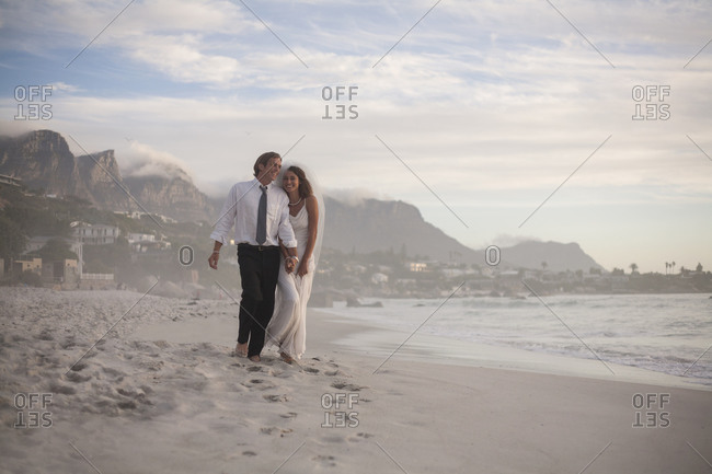 Happy newly married couple walking at beach against sky during sunset