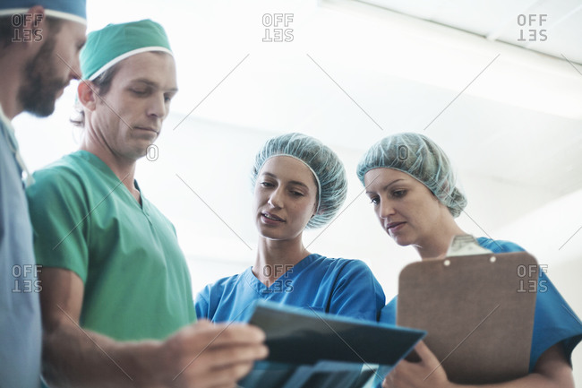 Team of surgeons discussing over medical x-ray image in hospital