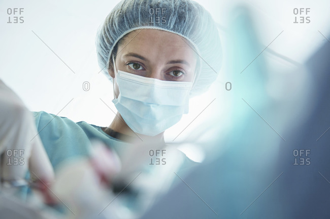 Confident female surgeon operating in intensive care unit at hospital