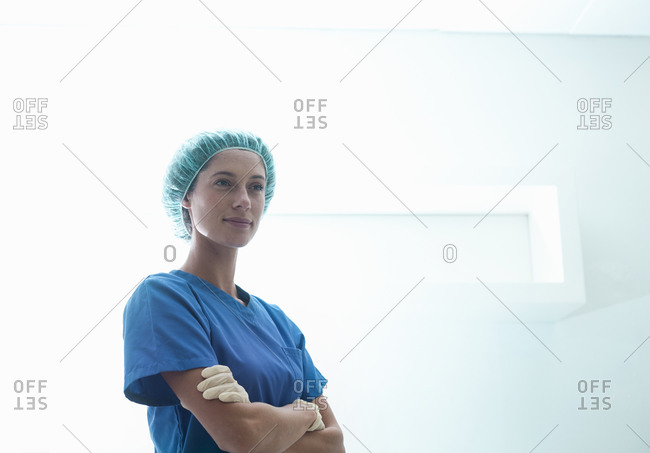 Confident female surgeon standing with arms crossed in intensive care unit at hospital
