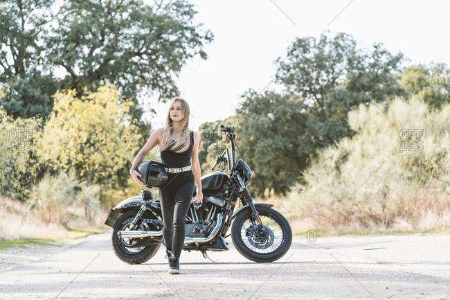 Beautiful biker woman walking while looking away against motorcycle on road