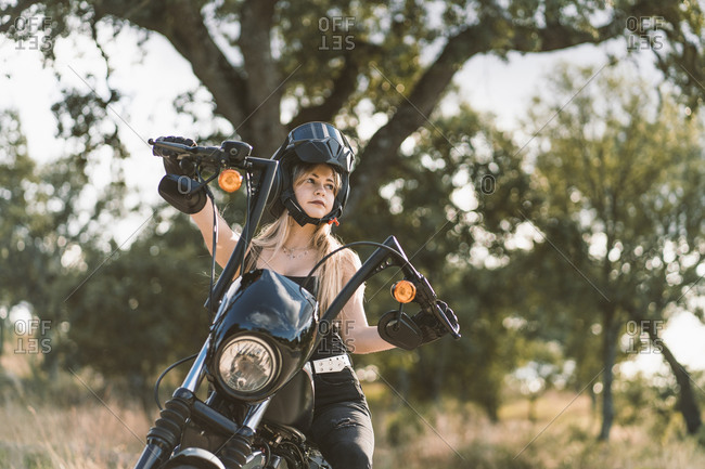Beautiful woman wearing crash helmet while sitting on motorcycle against tree