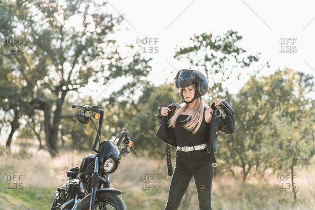 Blond young female biker wearing leather jacket while standing by motorcycle