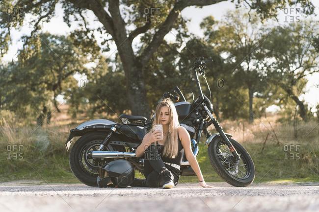 Blond female biker using smart phone while sitting against motorcycle on roadside