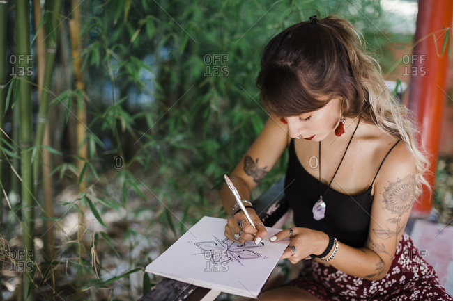 Woman drawing in book while sitting at park