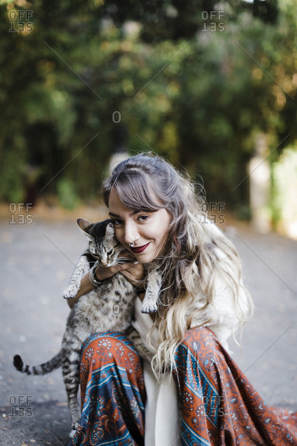 Woman embracing cat while sitting on road