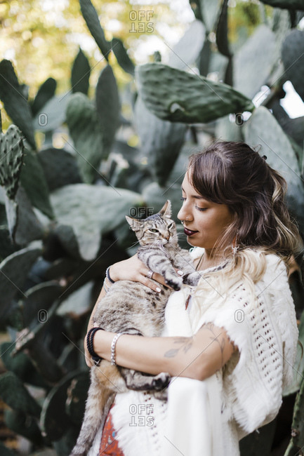 Woman holding cat while standing against plant