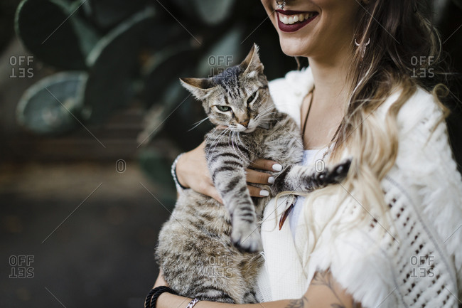 Smiling woman holding cat while standing against plant