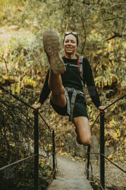 Smiling woman swinging on bridge railing at Sierra De Hornachuelos- Cordoba- Spain