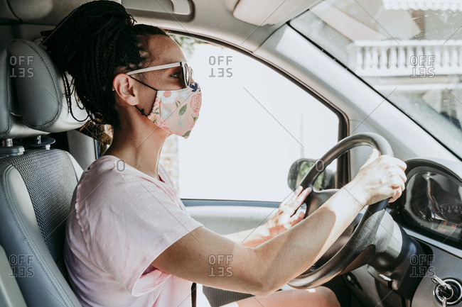 Woman wearing protective mask while driving car in city on sunny day