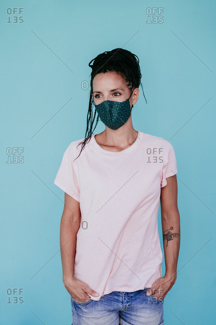 Caucasian woman wearing protective face mask looking away while standing with hands in pockets against turquoise background