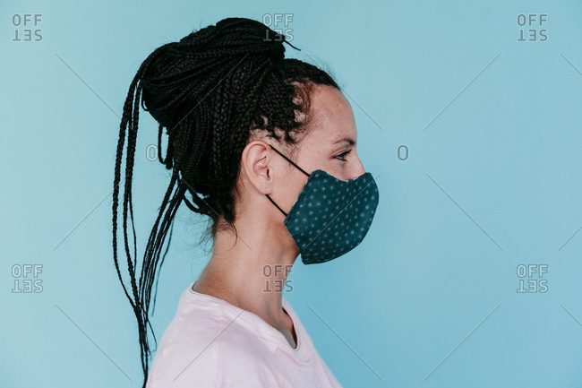 Woman wearing protective face mask with hair bun against turquoise background