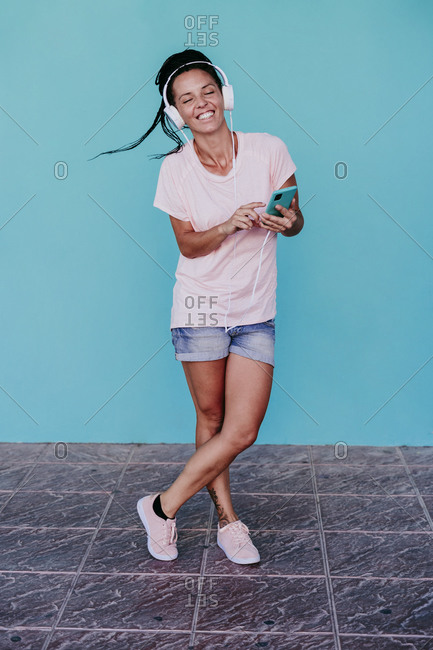 Beautiful woman enjoying music through headphones while standing legs crossed against turquoise wall