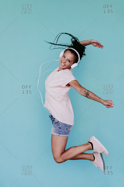 Excited woman jumping while listening music through headphones against turquoise background