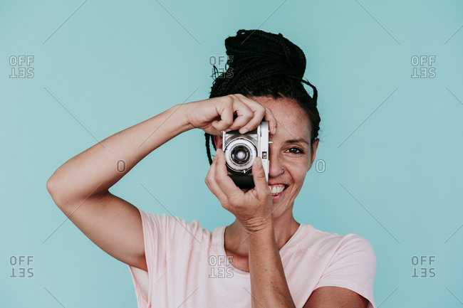 Smiling beautiful woman photographing with old-fashioned camera against turquoise background