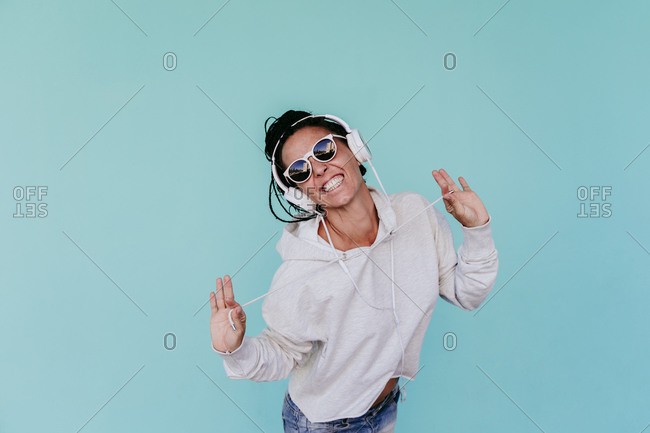Cheerful woman listening music while pulling strings against turquoise background