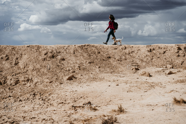 Spain- Navarre- Young woman hiking with dog in Bardenas Reales