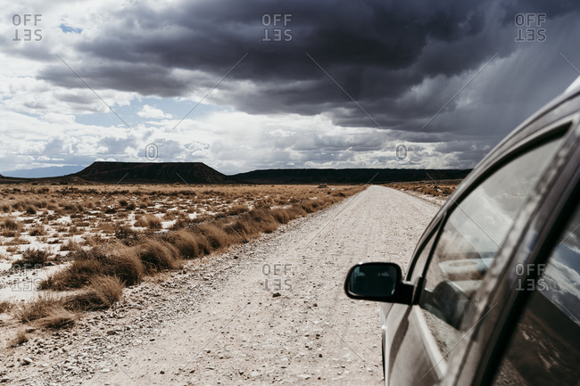Spain- Navarre- Storm clouds over car driving along empty dirt road in Bardenas Reales