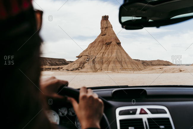 Spain- Navarre- Young woman driving car toward sandstone rock formation in Bardenas Reales