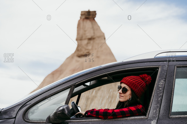 Young woman sitting inside car in Bardenas Reales