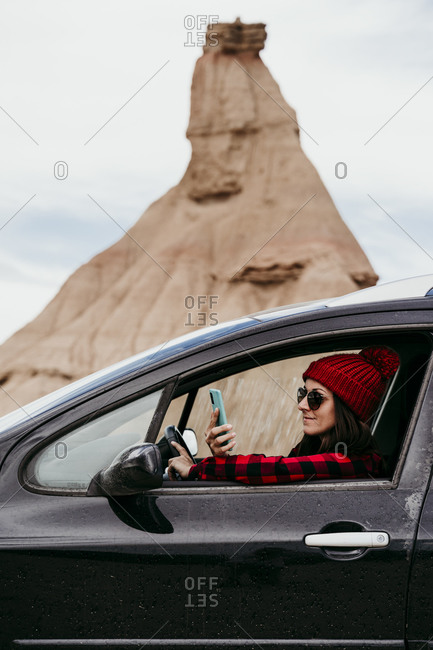 Young woman using smart phone inside car in Bardenas Reales