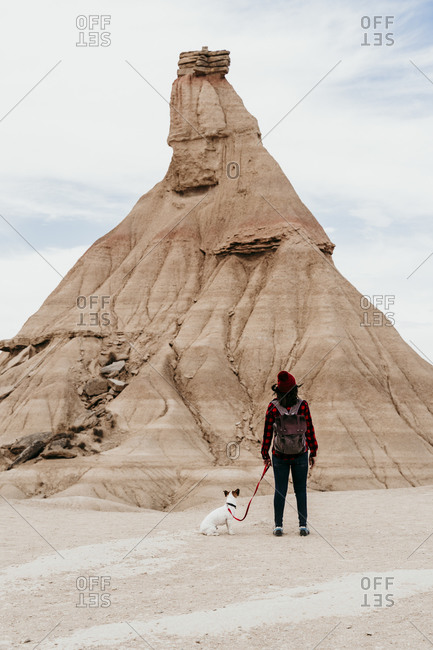 Spain- Navarre- Female backpacker standing with dog in front of sandstone rock formation in Bardenas Reales