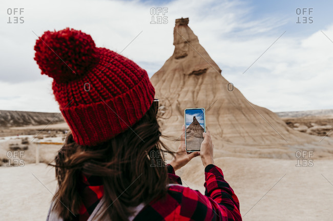 Spain- Navarre- Female tourist taking smart phone photos of sandstone rock formation in Bardenas Reales