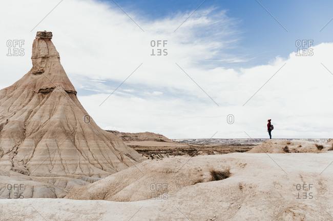 Spain- Navarre- Female backpacker admiring sandstone rock formation in Bardenas Reales