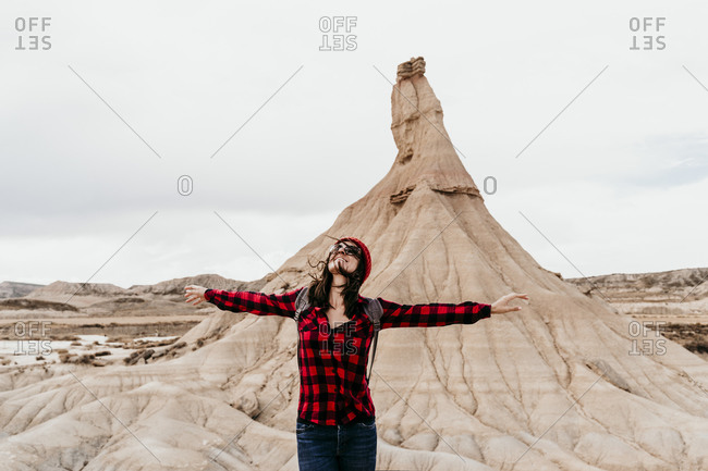 Spain- Navarre- Portrait of female tourist standing with raised arms in front of sandstone rock formation in Bardenas Reales